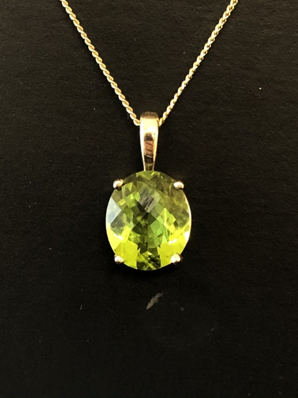 An oval peridot pendant on a gold bale