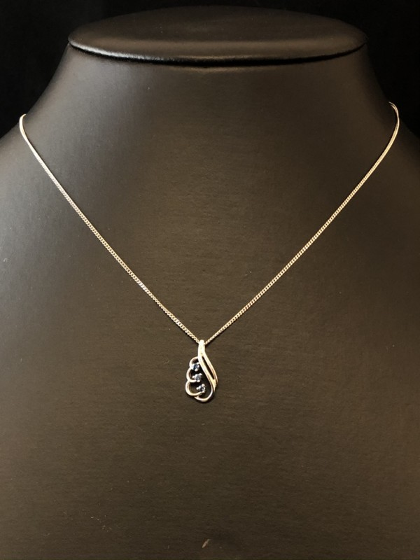 A white gold pendant with three small sapphires